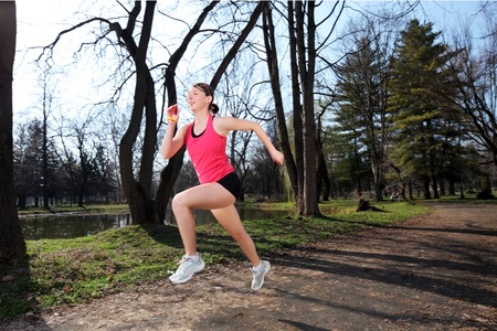 Panning shot of a female runner running outdoors photo