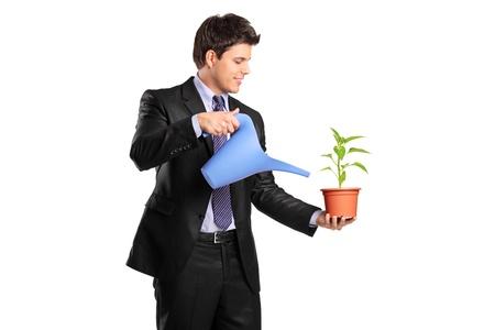 regando plantas: Un joven empresario verter agua sobre una flor aislada en blanco Foto de archivo