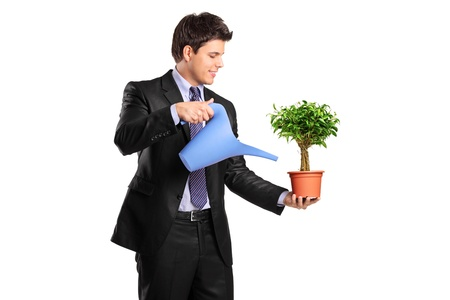 watering pot: A businessman holding a watering can and flower pot isolated on white background