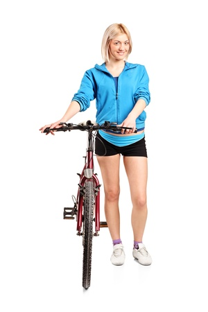 A blond female posing next to a bicycle isolated on white background photo