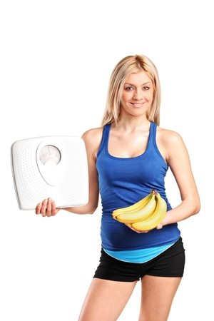 A happy young athlete holding a weight scale and bananas isolated against white background photo