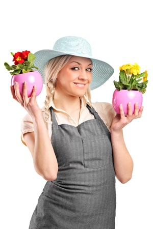 A smiling female gardener holding two potted plants isolated against white background photo