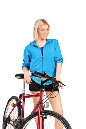 A smiling female posing next to a bicycle isolated against white background photo