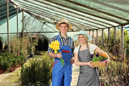 horticulturist: Male and female gardeners holding flower pots in a garden