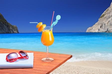 exotic: C�ctel naranja en una tabla de playa en la playa de Navagio en la isla de Zante, Grecia Foto de archivo