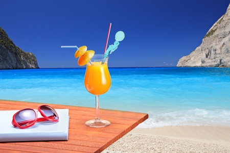 Orange cocktail on a beach table at Navagio beach on Zakynthos island, Greece Stock Photo