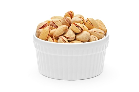 Salted and roasted pistachio nuts in a porcelain bowl isolated on white background  photo