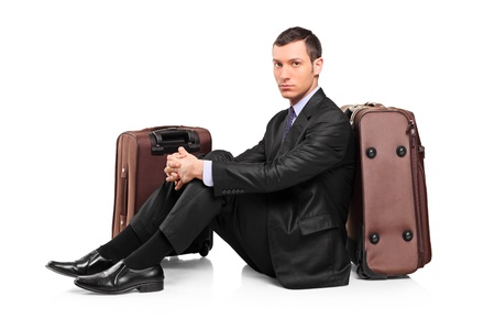 A business traveler waiting seated next to suitcases isolated on white background photo