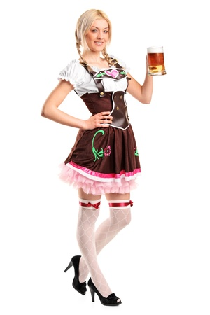 octoberfest: A full length portrait of a beautiful woman wearing a traditional costume holding a beer glass isolated on white