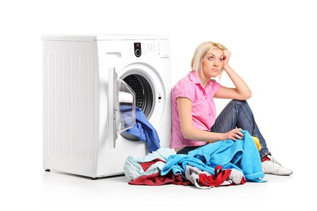 dirty blond: A thoughtful young woman with clothes seated next to a washing machine isolated on white background Stock Photo