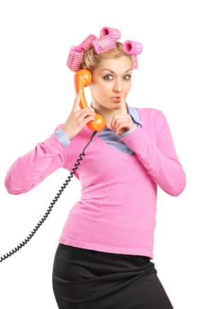 A woman with hair rollers talking on a phone with finger on her lips isolated on white background photo