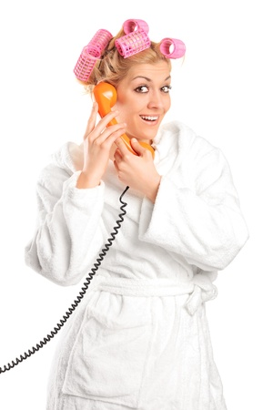 A young woman in a bathrobe with hair rollers gossiping on a phone isolated on white background Stock Photo - 9350067
