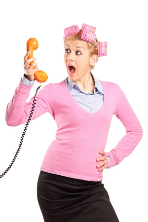 A young woman with hair rollers yelling on a phone isolated on white background photo