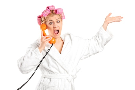 Angry woman in a bathrobe with hair rollers yelling on a phone isolated on white background photo