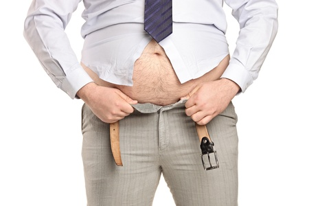 Overweight man trying to fasten too small clothes isolated on white background photo