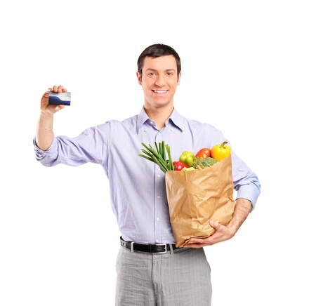 Smiling man holding a credit card and a bag full with vegetables isolated on white background photo