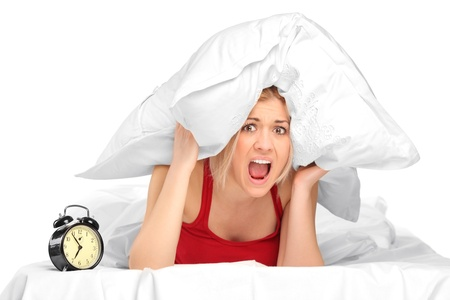 bothered: Woman screaming and covering her ears with pillow because of noise Stock Photo