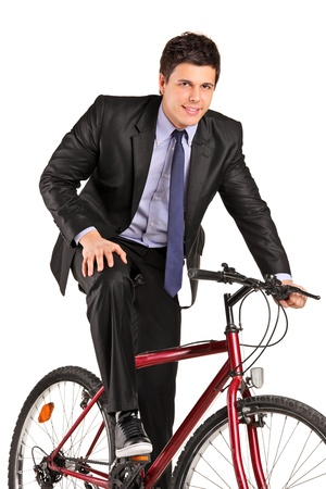 A young businessman posing on a bicycle isolated on white background photo