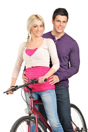A young couple in love posing on a bike isolated on white background Stock Photo - 9405381