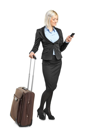 Full length portrait of a businesswoman carrying a suitcase and writing a sms isolated on white background photo