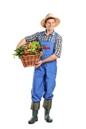 農家: 白い背景で隔離の野菜がいっぱい入ったかごを保持している農夫の完全な長さの肖像画