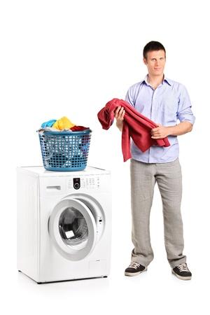 Laundry: Retrato de longitud completa de un hombre sosteniendo una blusa y una m�quina de lavar aislados en blanco