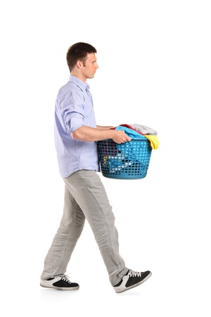 household tasks: Full length portrait of a young man carrying a laundry basket isolated on white background