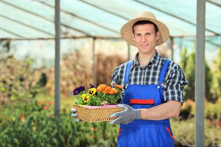 Male gardener holding flower pots in a garden Stock Photo - 9405384