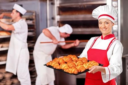 A female baker holding freshly baked croissants in bakery Stock Photo - 9468743