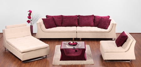 A studio shot of a modern furniture decorated with red pillows photo
