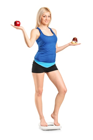 A woman holding an apple and slice of cake, standing on a weight scale, isolated against white background photo