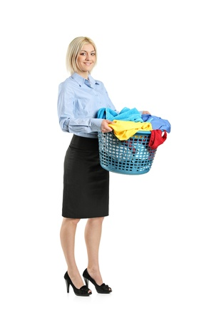 dirty clothes: Full length portrait of a young smiling woman holding a laundry basket isolated on white background
