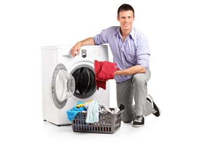 man machine: Young man putting clothes into washing machine and smiling isolated on white background