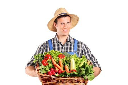 A farmer holding a basket full of vegetables isolated on white background photo