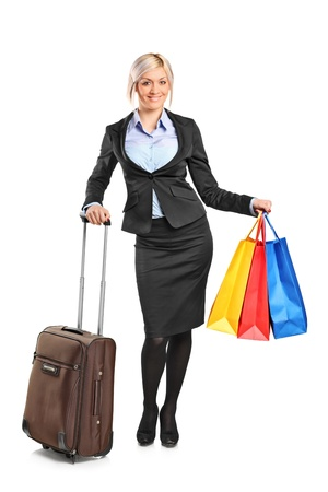 Full length portrait of a businesswoman holding a suitcase and shopping bags isolated on white background photo
