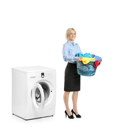 launder: Retrato de longitud completa de una mujer de pie junto a una m�quina de lavar aislada sobre fondo blanco
