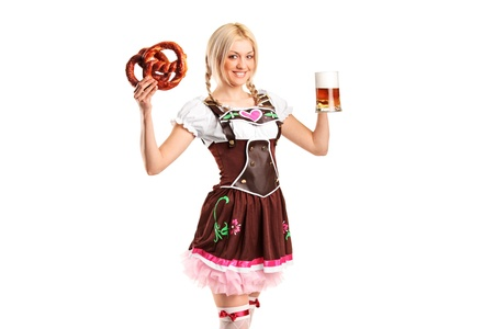 A beautiful woman in a traditional costume holding a beer and pretzel isolated on white photo