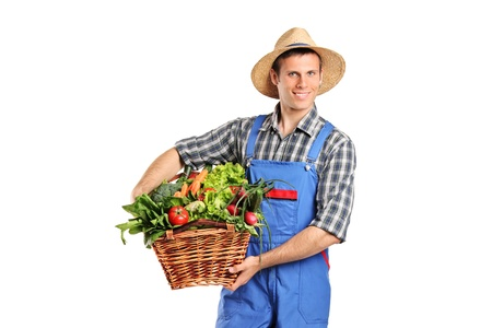 Farmer holding a basket full of vegetables isolated on white background photo