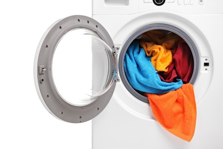 A close up of a washing machine loaded with clothes isolated on white background photo