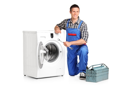 A repairman holding a spanner and posing next to a washing machine isolated on white background  Stock Photo