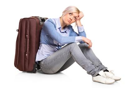 Una ragazza triste turistico seduta accanto a una valigia isolata su sfondo bianco
