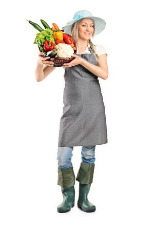 Full length portrait of a female farmer holding a basket full of vegetables isolated on white background photo