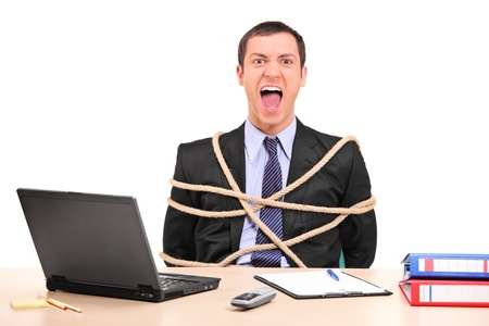 trapped: A businessman tied up with rope in the office isolated on white background Stock Photo