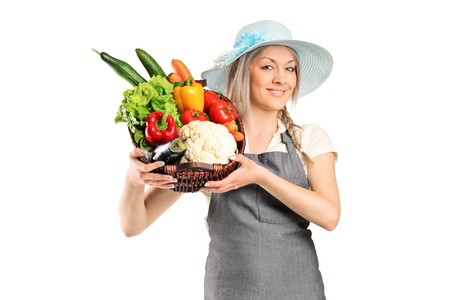 A female farmer holding a basket full of vegetables isolated on white background photo