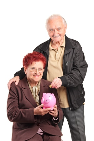 A mature people putting a coin into a piggy bank isolated on white background photo