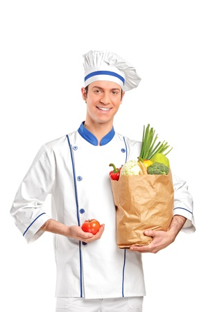 A smiling chef holding a tomato and paper bag full with vegetables isolated on white background Stock Photo - 9605104