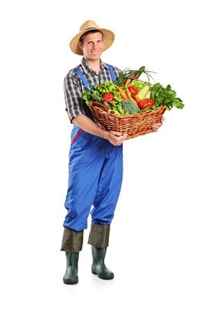 vegetable basket: Full length portrait of a farmer holding a basket of vegetables isolated on white background Stock Photo
