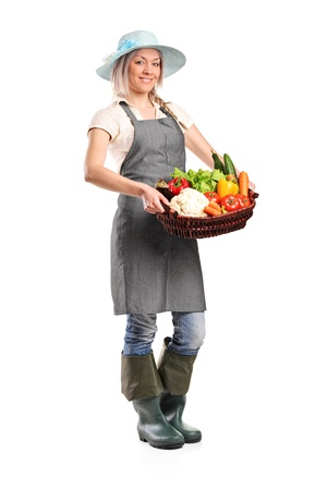 Full length portrait of a female farmer holding a basket of vegetables isolated on white background photo