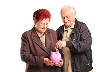 investing: A happy old couple putting a coin into a piggy bank isolated on white background