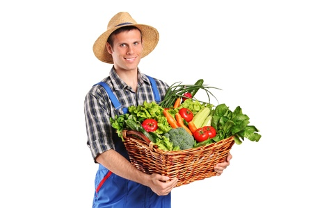 Smiling farmer holding a basket of vegetables isolated on white background photo